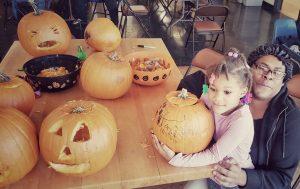Community members carving pumpkins